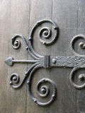 Ancient metal door hinge. Ancient wrought iron ornate door hinge on old wooden door royalty free stock image