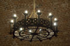 An ancient Middle Ages chandelier on a brick castle ceiling. Latvia Turaidas castle tower Stock Photography