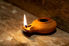 Ancient Middle Eastern oil lamp made in clay on wood table stock photo