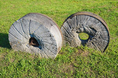 Ancient millstone on the grass, natural background Stock Photo