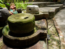 Ancient millstone have green lichen around and Ancient millstone Royalty Free Stock Photo