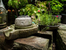 Ancient millstone have green lichen around and Ancient millstone put on old wooden boards. Stock Photos