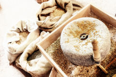 Ancient millstone with wheat grains Stock Images