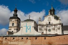 Ancient monastery of Discalced Carmelites, cathedral and fortres. S wall on background of blue cloudy sky. City Berdychiv, Ukraine. Tourist attraction. Place of Stock Image