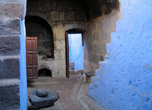 Ancient monastery kitchen. Ancient kitchen in the monastery Santa Catalina, Arequipa, Peru, with blue walls, an open hearth and a grind stone to grind grain, the Stock Photo