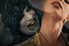 Ancient monster vampire demon bites a woman neck. Halloween fant. Ancient monster vampire demon holds beautiful women and preparing to bites her neck. Halloween Royalty Free Stock Photos