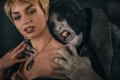 Ancient monster vampire demon bites a woman neck. Halloween fant Stock Image
