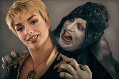 Ancient monster vampire demon bites a woman neck. Halloween fant. Ancient monster vampire demon holds beautiful women and preparing to bites her neck. Halloween Royalty Free Stock Images