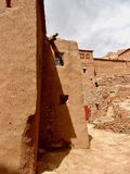 Ancient Moroccan village to abandonment. Narrow streets and brick houses of raw earth. Buildings and streets in dark ocher color. Small windows for protection Stock Photo