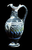 Ancient mosaic glass flask isolated on black Stock Images