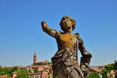 Ancient moss-covered statue in the Berbie palace,. Ancient moss-covered statue in the gardens of the Berbie palace in Albi with the blurred old city in Stock Image