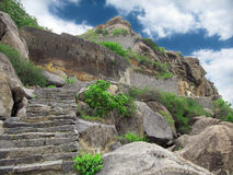 Ancient mountain fortress. Ancient East Indian mountain ruins before cloudy blue sky Stock Image
