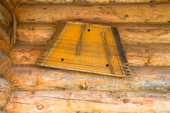 Ancient musical instrument gusli on the wooden wall Royalty Free Stock Images