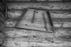Ancient musical instrument gusli on the wooden wall. Toned Stock Image