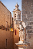 Ancient narrow street, the Carmelite convent and medieval statue Stock Photos