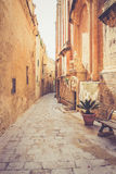 Ancient narrow street in Mdina, Malta. Warm color filter used Royalty Free Stock Photo