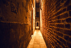 Ancient narrow streets and facades of old medieval buildings at night time close-up. Venice, Italy Stock Photos