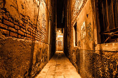 Ancient narrow streets and facades of old medieval buildings at night time close-up. Venice, Italy Stock Photography