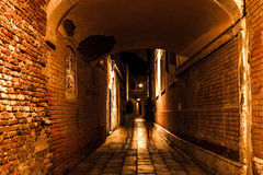 Ancient narrow streets and facades of old medieval buildings at night time close-up. Venice, Italy Royalty Free Stock Images