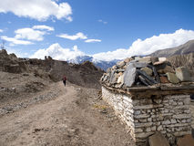 Ancient Nepal Mani Stones on the white brick wall and backpacker walking at distance Stock Image