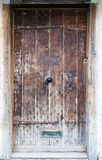 An ancient oak wood door with ornate metal handle Stock Photos
