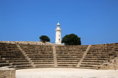 The ancient Odeon Amphitheatre with the lighthouse on the background. Paphos, Cyprus. Royalty Free Stock Photography