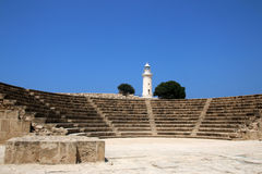 The ancient Odeon Amphitheatre with the lighthouse on the background. Paphos, Cyprus. Stock Photography