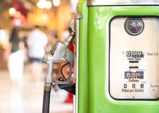 Ancient oil dispenser. Ancient petrol oil pump dispenser on blurred bokeh background Royalty Free Stock Image