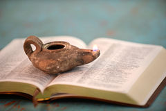 Ancient Oil Lamp on Open Bible Stock Images