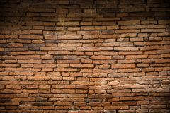 Ancient old brick wall decadent background. Dark dim light Stock Images