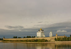 Ancient old fortress on the river bank bright clouds sky July 30rd 2016, Russia - Pskov Kremlin wall, Trinity Cathedral, Bell Towe Stock Photos