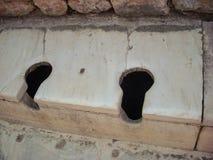 Ancient old roman stone marble toilet seats.  Royalty Free Stock Photo