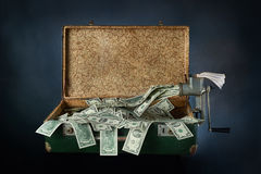Ancient old suitcase full of banknotes. Ancient old green suitcase full of banknotes on a blue background Stock Photo