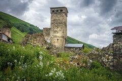 Ancient old Svan tower in mountain village on green grassy hill, Svaneti region in Georgia. Royalty Free Stock Photography