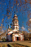 Ancient Orthodox church against birch branches with the dried-up. The ancient temple in the clear afternoon against the blue sky with branches of birches in the Royalty Free Stock Photography