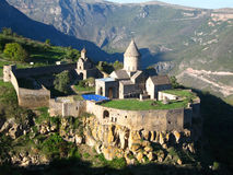 Ancient orthodox stone monastery in Armenia, Tatev monastery, made of gray brick. Beautiful landscape, sunny day, deep blue sky with some clouds, green royalty free stock photos