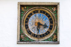 Ancient outdoor clock on white wall in Tallinn Stock Image