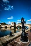 Ancient packhorse bridge. Ancient stone packhorse bridge over a main river beneath a sunny sky Stock Image
