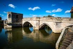 Ancient packhorse bridge. Ancient stone packhorse bridge over a main river beneath a sunny sky Royalty Free Stock Image