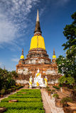 Ancient pagoda. Behind white buddha statue in the garden at Ayutthaya, thailand Royalty Free Stock Image