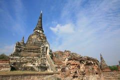 Ancient pagoda near ruined brick wall. Ornament: ancient pagoda near ruined brick wall against blue sky at wat Phra Sri Sanphet, Ayutthaya, Thailand Royalty Free Stock Images