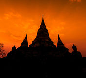 Ancient pagoda at the temple with sunset sky, Thailand Stock Photo