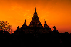 Ancient pagoda at the temple with sunset sky, Thailand Stock Photography
