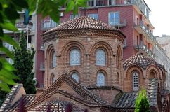 Ancient Panagia Chalkeon church, XI century, on a background of modern buildings, Thessaloniki, Greece stock image