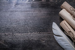 Ancient paper scrolls feather on wooden board. Copyspace stock photography