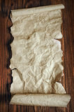 The ancient parchment or unrolled scroll. On a wooden background Stock Image
