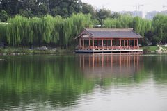 Ancient park with a lake and willow trees Stock Photo