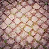 Ancient pavement in Rome vintage effect. Stone roadway with growing through. Royalty Free Stock Photography