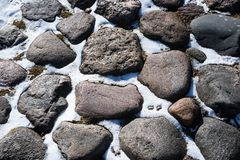 Ancient paving stone from a cobblestone on a snowy day Stock Photos