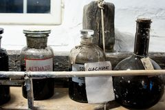 ancient pharmacist and chemical ampoules stored on wooden and dusty shelves. elements for chemicals stock photos